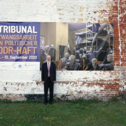 Thomas Schirrmacher in front of the poster of the tribunal on the outside wall of the former Cottbus penitentiary © BQ/Martin Warnecke